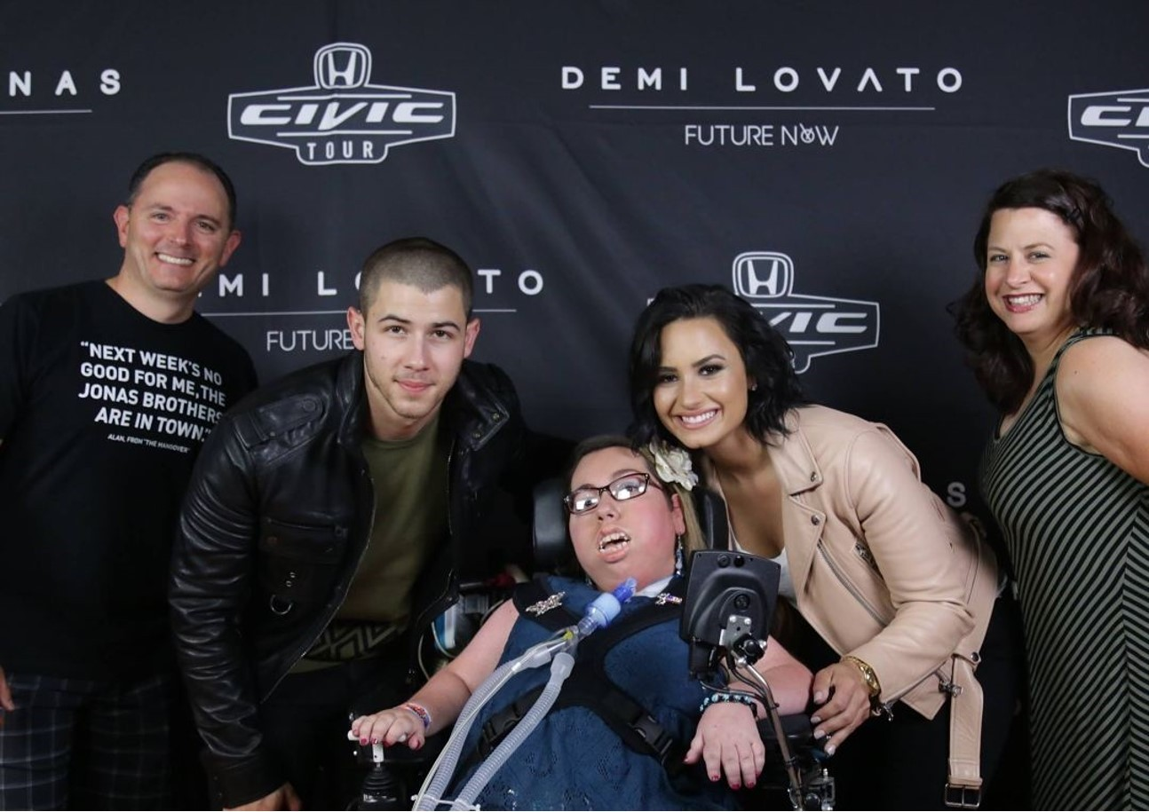 The Calise family, Michael, Corinna, and Michelle, with Nick Jonas and Demi Lovato