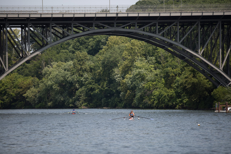 a rower going under a bridge on the river